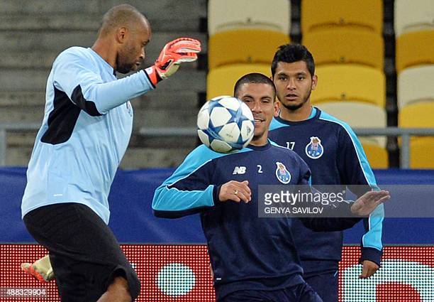 FC Porto's goalkeeper Helton vies for the ball with Maxi Pereira and Jesus Corona during a training session at the Olimpiysky stadium in Kiev on...