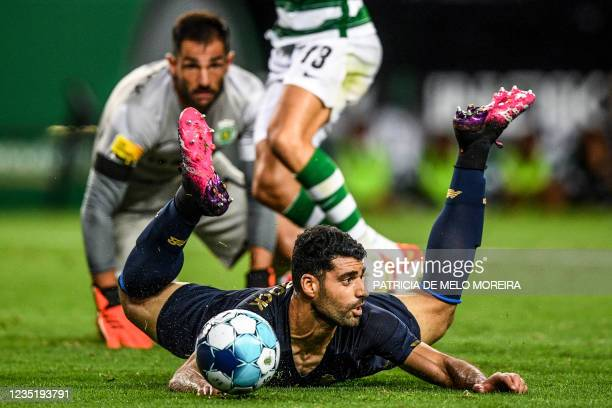 Porto's Iranian forward Mehdi Taremi falls down on the pitch during the Portuguese League football match between Sporting CP and FC Porto at the Jose...