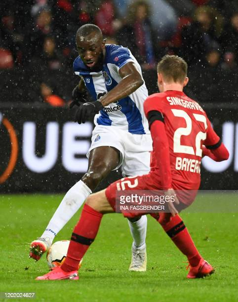 FC Porto's Malian forward Moussa Marega and Leverkusen's Dutch defender Daley Sinkgraven vie for the ball during the Europa League last 32 first leg...