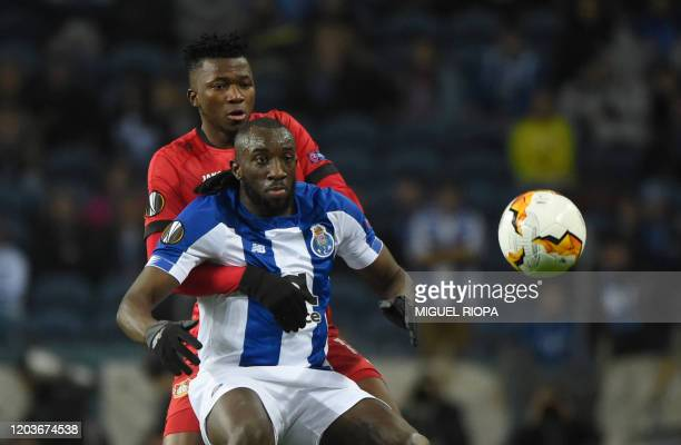 FC Porto's Malian forward Moussa Marega vies with Bayer Leverkusen's Burkinabe defender Edmond Tapsoba during the UEFA Europa League round of 32...