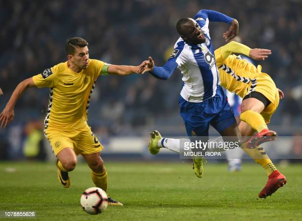 Porto's Malian forward Moussa Marega vies with Nacional's Serbian defender Lazar Rosic beside Nacional's Portuguese defender Nuno Campos during the...