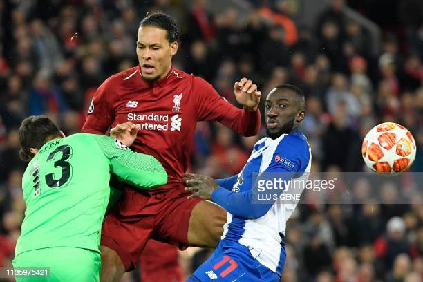 Porto's Malian striker Moussa Marega vies for the ball with Liverpool's Dutch defender Virgil van Dijk and Liverpool's Brazilian goalkeeper Alisson...