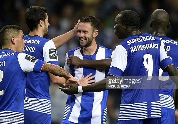 Porto's Mexican defender Miguel Layun is congratulated by teammates after scoring a goal during the Portuguese league football match FC Porto vs...