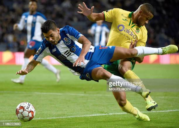 Porto's Mexican forward Jesus Corona 'Tecatito' falls down as is tackled by Pacos Ferreira's Brazilian defender Bruno Santos during the Portuguese...