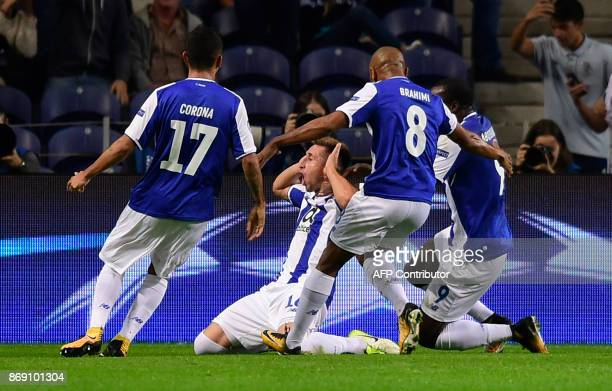 Porto's Mexican midfielder Hector Herrera celebrates with teammates after scoring a goal during the UEFA Champions League group G football match FC...