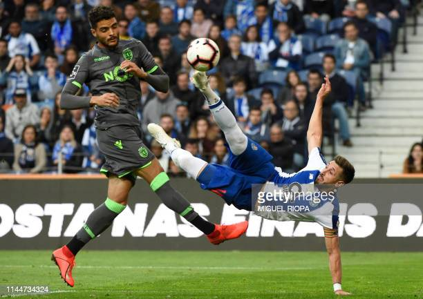 Porto's Mexican midfielder Hector Herrera kicks the ball next to Sporting's Portuguese defender Tiago Ilori to score a goal during the Portuguese...