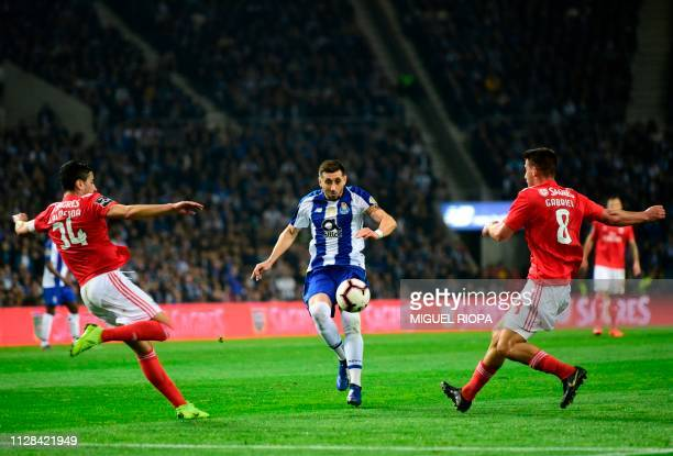 Porto's Mexican midfielder Hector Herrera runs for the ball between Benfica's Portuguese defender Andre Almeida and teammate Brazilian midfielder...