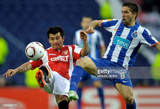 FC Porto's midfielder Joao Moutinho vies with Sevilla's Chilean midfielder Gary Medel during their UEFA Europa League round of 32 football match at...