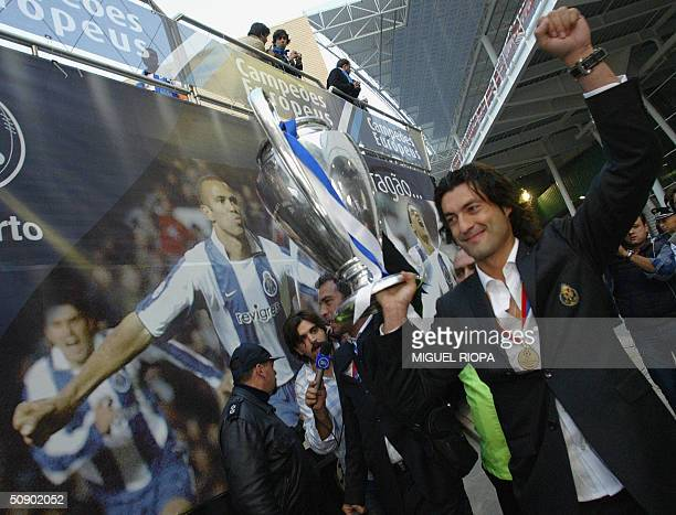 Porto's player Vitor Baia arrive at the Porto airport northern Portugal 27 May 2004 holding to supporters the trophy of the Champions League after...