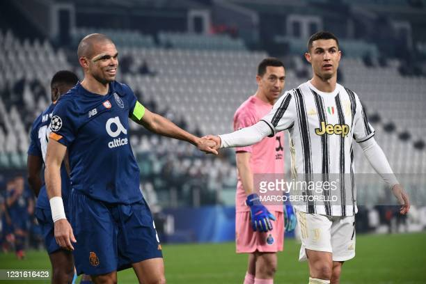 Porto's Portugese defender Pepe , wearing a band-aid after receiving a headbutt on a corner kick, holds hand with Juventus' Portuguese forward...