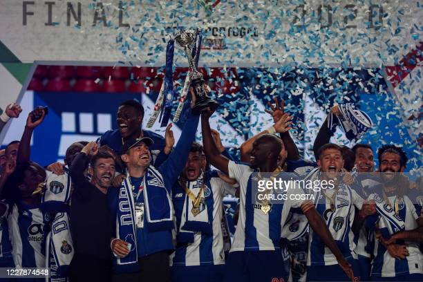 FC Porto's Portuguese coach Sergio Conceicao holds the trophy with Spanish former FC Porto's goalkeeper Iker Casillas and FC Porto's Portuguese...