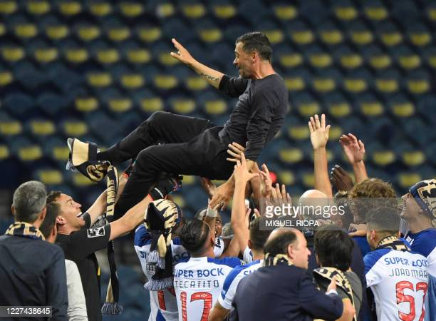 Porto's Portuguese coach Sergio Conceicao is tossed in the air by players as they celebrate clinching their 29th Portuguese Primeira Liga title at...