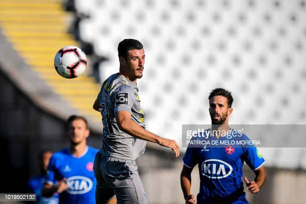 Porto's Portuguese forward Andre Pereira heads the ball during the Portuguese League football match between Os Belenenses and Porto at the Jamor...