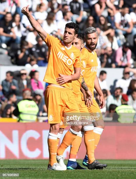 Porto's Spanish defender Ivan Marcano celebrates with teammates after scoring a goal during the Portuguese league football match between Vitoria SC...