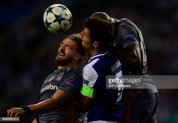 Porto's Spanish defender Ivan Marcano jumps for the ball with Besiktas' defender Caner Erkin and teammate Canadian midfielder Atiba Hutchinson during...