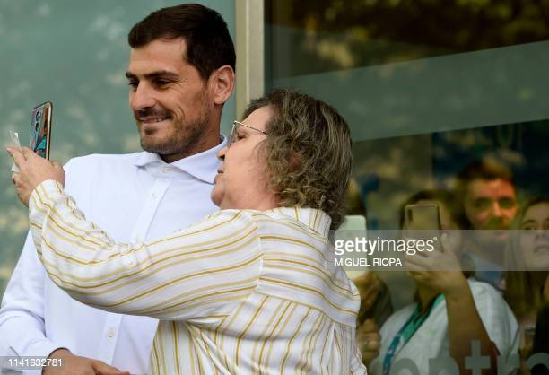 Porto's Spanish goalkeeper Iker Casillas takes a selfie photo with a woman after leaving a hospital in Porto on May 06 2019 after recovering from a...