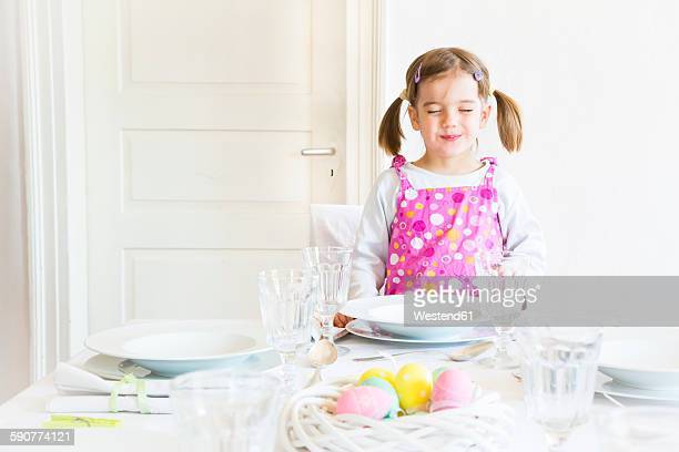 Portrai of smiling little with closed eyes girl standing behind laid table