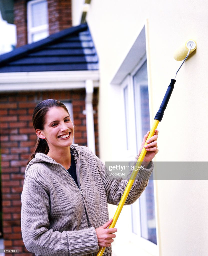 Portrait A Woman Painting An Outside Wall With A Roller Brush : Stock Photo