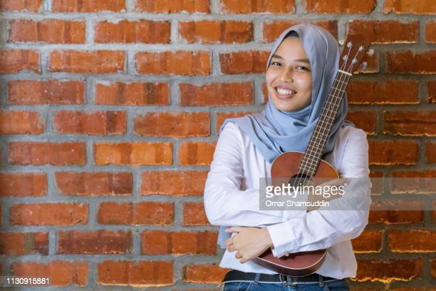 Portrait a young muslim woman and musician with ukulele