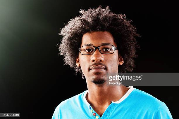 Portrait against black of serious afro-haired young man with spectacles