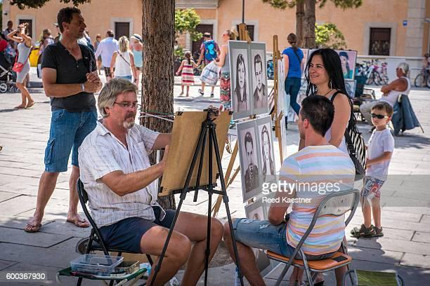 A  portrait artist works on a model as others watch in Palma de Mallorca, Spain