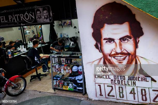 A portrait artwork depicting the drug lord Pablo Escobar is seen painted on the wall next to a barber shop in the Pablo Escobar neighborhood in...
