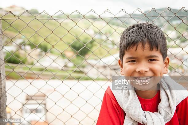 Portrait. Asian boy in urban city streets. Happy, smiling.