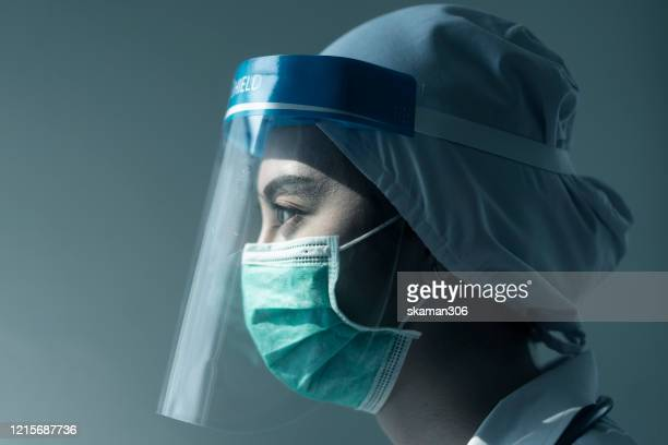 portrait asian female doctor wearing face shield and ppe suit and holding syringe for coronavirus outbreak or covid-19, concept of covid-19 quarantine - フェイスシールド ストックフォトと画像