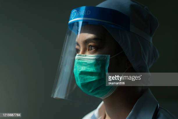 portrait asian female doctor wearing face shield and ppe suit and holding syringe for coronavirus outbreak or covid-19, concept of covid-19 quarantine - scientificsubjects stock pictures, royalty-free photos & images