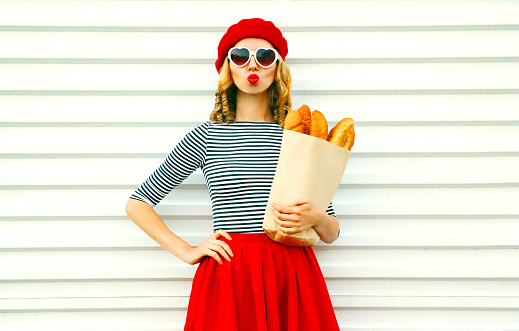 Portrait beautiful young woman blowing lips making air kiss wearing red beret holding in hands paper bag with long white bread baguette on white wall background 1073264136