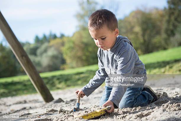 Portrait boy playing shovel sieve sand playground