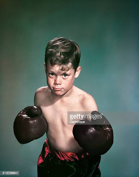 Portrait boy wearing boxing gloves and trunks Los Angeles California 1949