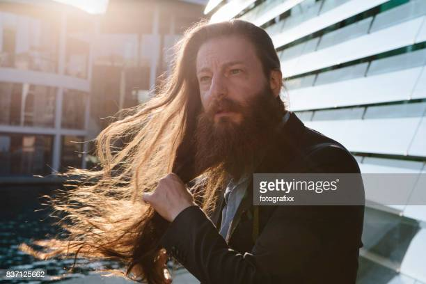 portrait: businessman with long hair and beard, back lit, rebellion - long hair stock pictures, royalty-free photos & images
