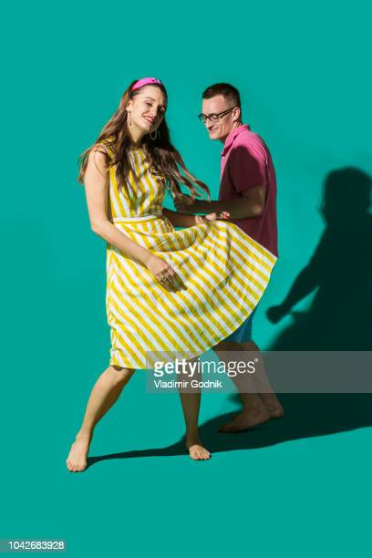 portrait carefree couple dancing against turquoise background - men wearing dresses stock photos and pictures