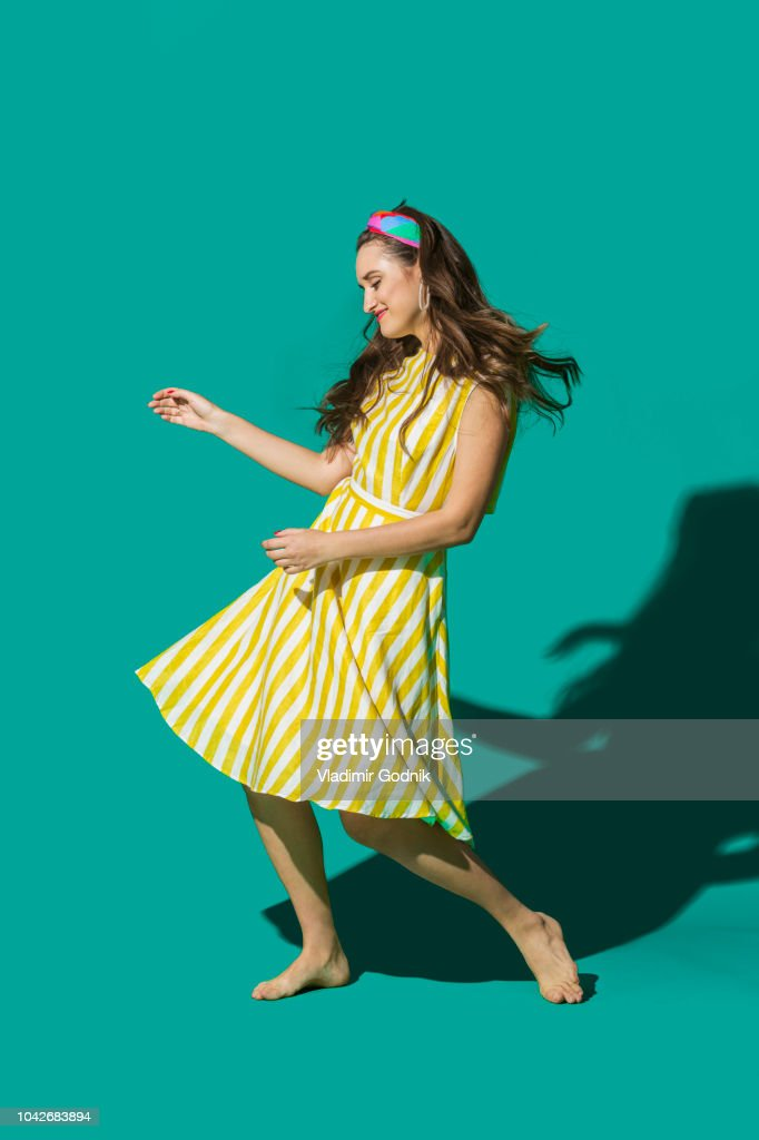 Portrait carefree young woman in striped dress dancing against turquoise background : Stock Photo