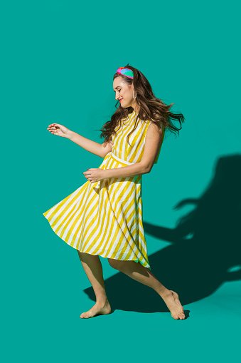 Portrait carefree young woman in striped dress dancing against turquoise background - gettyimageskorea
