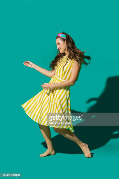 Portrait carefree young woman in striped dress dancing against turquoise background