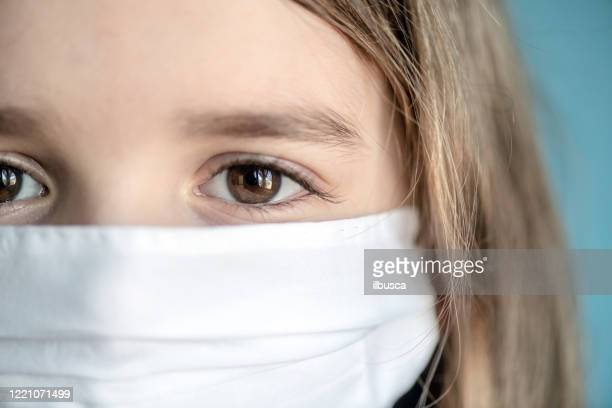 portrait close up of little girl child wearing protective mask during pandemic - cloth mask stock pictures, royalty-free photos & images