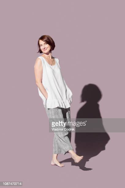 portrait confident, barefoot woman against purple background - hands in pockets stock pictures, royalty-free photos & images