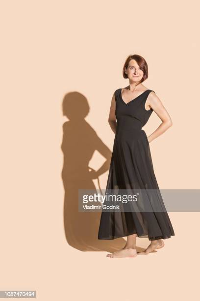 portrait confident, barefoot woman in black dress - beige background stock pictures, royalty-free photos & images