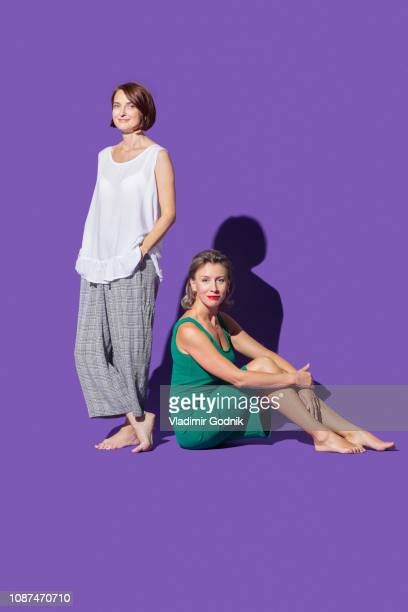portrait confident, barefoot women against purple background - pies descalzos mujer fotografías e imágenes de stock