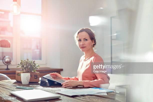Portrait confident businesswoman using digital tablet at desk in office