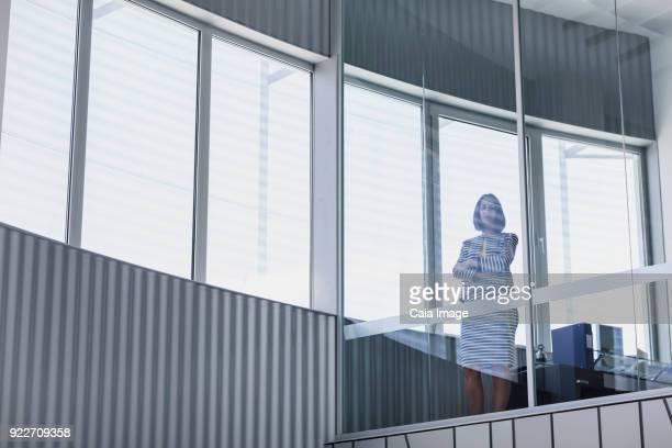 Portrait confident CEO businesswoman standing at modern office window