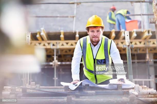 Portrait confident engineer with blueprints at construction site