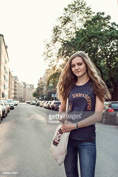 Portrait confident female high school student standing on city street