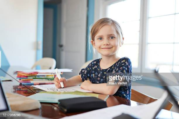portrait confident girl doing homework at dining table - bambine femmine foto e immagini stock