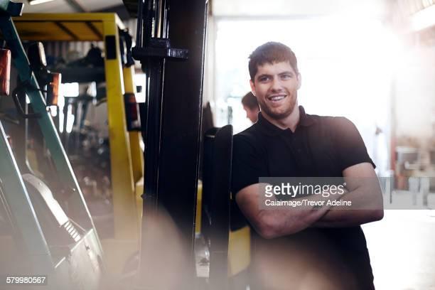 Portrait confident mechanic leaning on forklift in auto repair shop