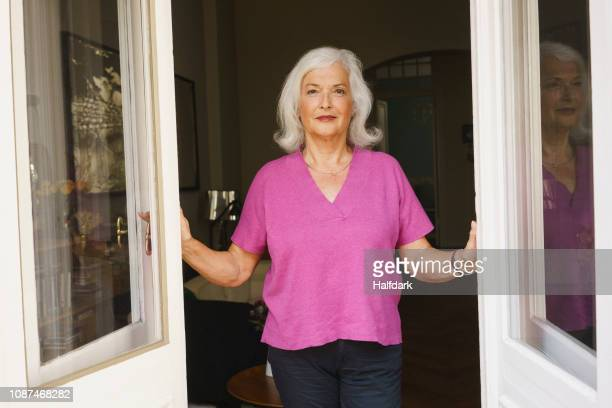portrait confident senior woman standing in patio doorway - 65 69 jahre stock-fotos und bilder