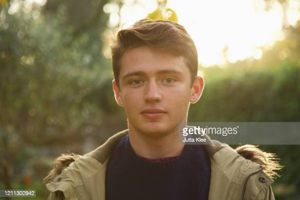 portrait confident teenage boy in park - one teenage boy only stock pictures, royalty-free photos & images