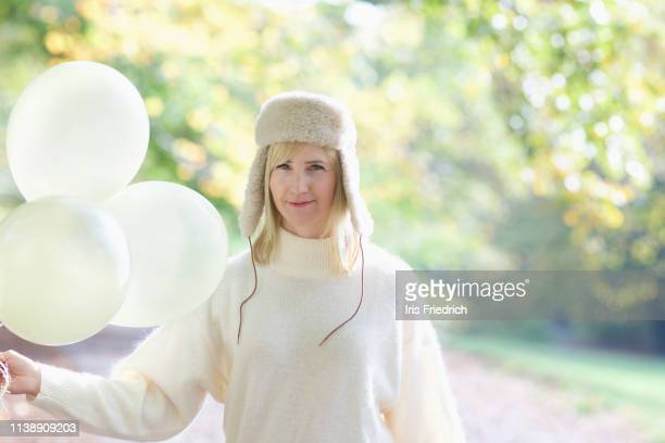 portrait confident woman in white fur hat holding bunch of balloons in park - セーター ストックフォトと画像
